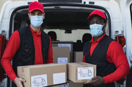 Young delivery men carrying cardboard box while wearing face mask to avoid  virus spread - People working with fast deliver during  virus outbreak
