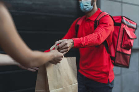 Rider man delivering meal to customers with electric scooter while wearing face mask during  virus outbreak - Ecological fast delivery food concept