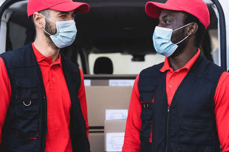 Young delivery men working while wearing face mask to avoid  virus spread - People working with fast deliver during  virus outbreak 版權商用圖片