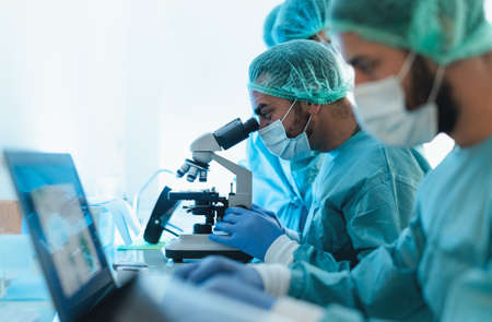 Doctors wearing personal protective equipment working in laboratory using computer and examining  through microscope - Science and technology concept
