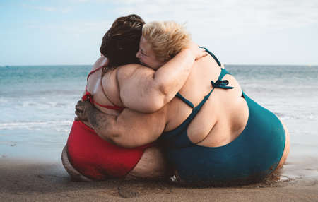 Happy plus size women having fun embracing on the beach during vacation summer holidays - Curvy confident people lifestyle concept
