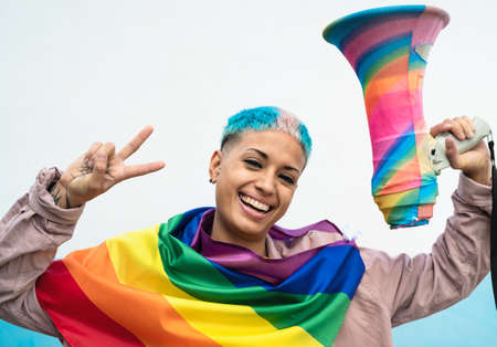 Young woman celebrating gay pride event wearing rainbow flag symbol of Lgbt social movement 版權商用圖片