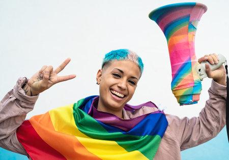 Young woman celebrating pride event wearing rainbow flag symbol of Lgbt social movement Reklamní fotografie
