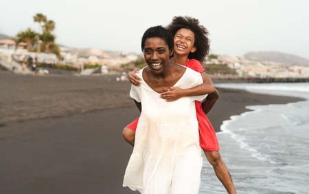 Happy African family on the beach during summer holidays - Afro American people having fun on vacation time - Parents love and travel lifestyle concept