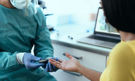 Medical worker checking glycemia test for diabetes to female patient during  virus outbreak - Healthcare concept 版權商用圖片