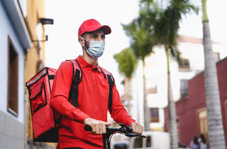 Rider man delivering meal with electric scooter in the city while wearing face mask during  virus outbreak - Ecological fast delivery food concept