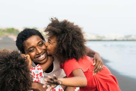获得愉快的非洲家庭获得在海滩的乐趣在暑假期间 - 享受假期日的亚伯士 - 父母爱和旅行生活方式概念