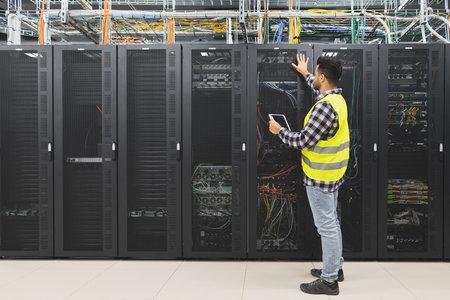 Male informatic engineer working inside server room database Banque d'images