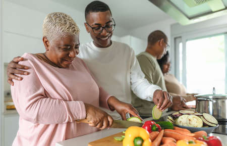 Happy African family having fun in modern kitchen preparing food recipe with fresh vegetables - Food and parents unity concept