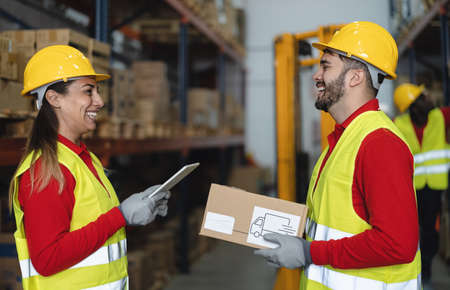 Warehouse workers doing inventory using digital tablet and loading delivery boxes plan - Logistic and industry concept Imagens