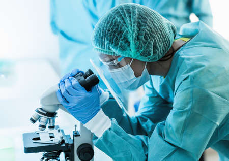 Female scientist examining through microscope in hospital laboratory - Science and technology concept