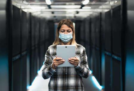 Female informatic engineer working inside server room database while wearing face mask during virus outbreak