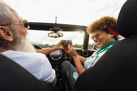 Happy senior couple having fun taking photo with old vintage camera while driving on new convertible car during road trip tour vacation