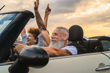 Happy senior couple having fun driving on new convertible car - Mature people enjoying time together during road trip tour vacation - Travel people lifestyle concept
