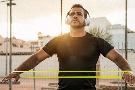 Latin man doing workout exercises session at sunset time - Young Hispanic male training hard while listening music with headphones