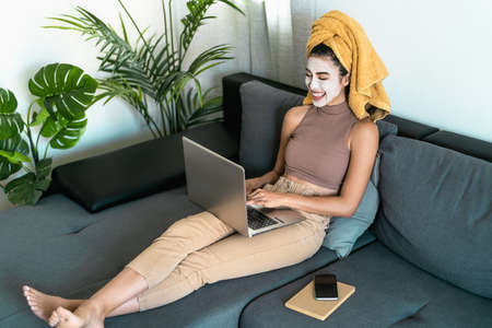Young woman using laptop while having skin care day at home