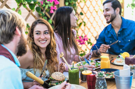 Happy friends lunching with healthy food in bar coffee brunch - Young people having fun eating meal and drinking fresh smoothies in restaurant - Health nutrition lifestyle concept