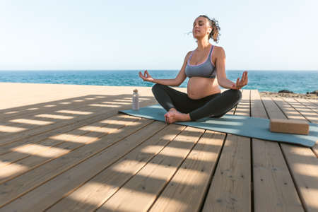 Young pregnant woman doing yoga session next the sea - Meditation and maternity concept