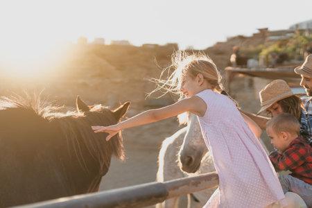 Happy family having fun with horses inside corral ranch 版權商用圖片