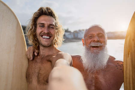 Happy fit surfers taking selfie while having fun surfing together at sunset time - Extreme sport lifestyle and friendship concept 版權商用圖片
