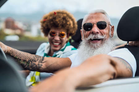 Happy senior couple having fun driving on new convertible car - Mature people enjoying time together during road trip tour vacation - Elderly lifestyle and travel culture concept
