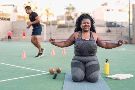 Curvy Afro woman doing workout exercises session - Young African female having fun training outdoor - Sporty people lifestyle concept