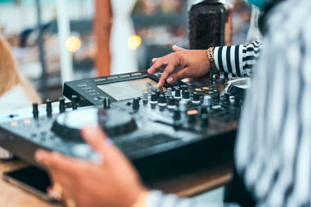 Close up dj hand mixing music at cocktail bar - Party nightlife concept