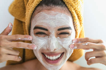 Young smiling woman applying cream on face - Happy girl having skin care spa day at home - Healthy beauty clean treatment and youth people lifestyle concept