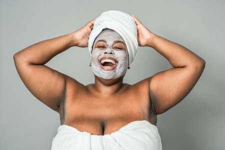 Happy curvy African woman having skin care spa day - Healthy beauty clean treatment and youth people lifestyle concept