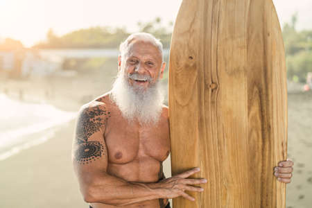 Senior male having fun surfing during sunset time - Fit retired man training with surfboard on the beach - Elderly healthy people lifestyle and extreme sport concept