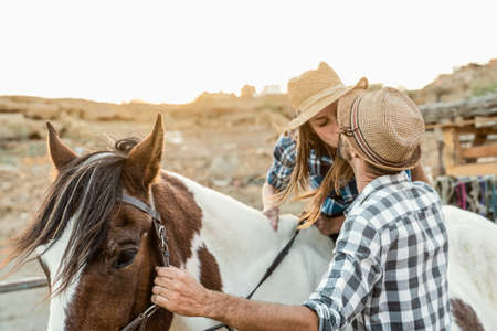 Happy couple of farmers kissing while riding on horse inside corral ranch