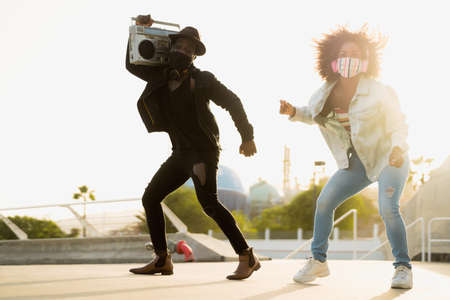 Young Afro friends dancing outdoor while listening to music with wireless headphones and vintage boombox