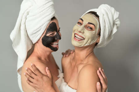 Happy middle age women with facial mask having skin care spa day - People selfcare lifestyle concept