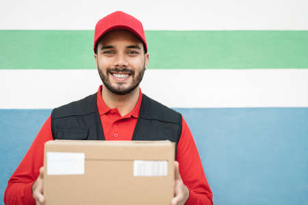 Young delivery man carrying cardboard box - People working with fast deliver transportation