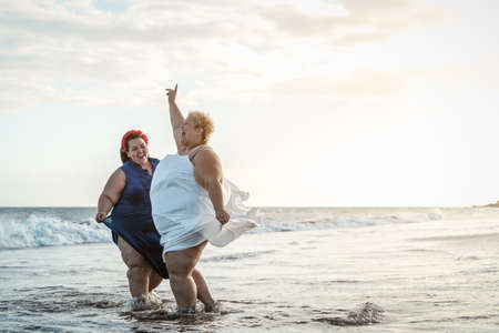 Happy plus size women having fun on the beach during summer vacation - Curvy confident people lifestyle concept 版權商用圖片