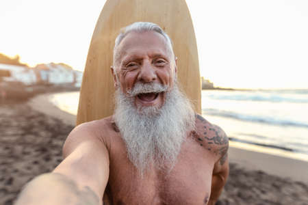 Happy senior surfer taking selfie while having fun surfing at sunset time - Elderly health people lifestyle and extreme sport concept 版權商用圖片