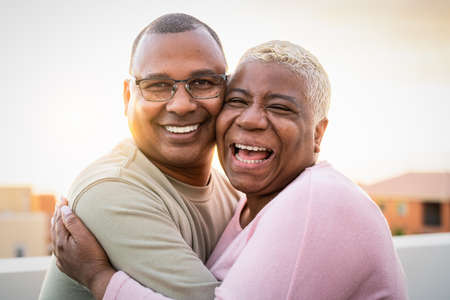 Happy Latin senior couple having romantic moment embracing on rooftop during sunset time - Elderly people love concept 版權商用圖片