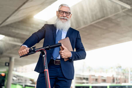 Senior business man going to work with electric scooter around city center