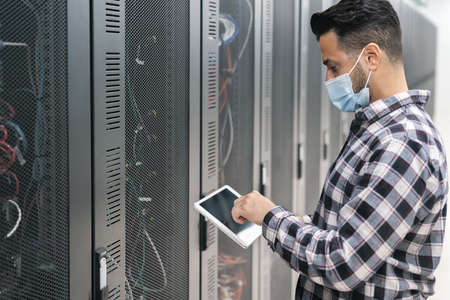 Male informatic engineer working inside server room database while wearing face mask during corona virus outbreak