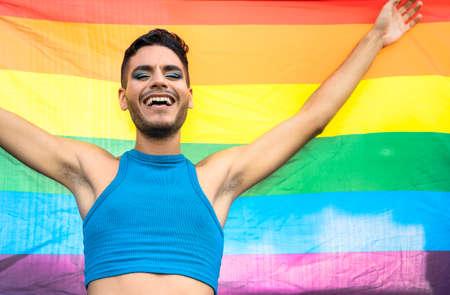 Happy homosexual man celebrating gay pride holding rainbow flag symbol of LGBTQ community 版權商用圖片