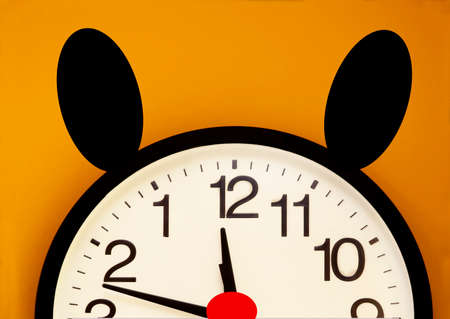 Wall clock with the order of the number inverted, black ears and a red nose photo