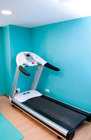 Electric tapis roulant inside a gym with a bright blue background