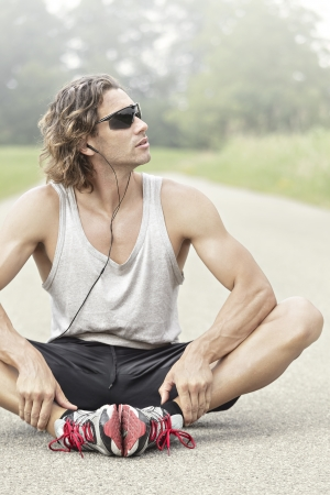long hair man: athlete with sunglasses looks away listening to music
