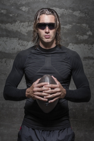 half ball: sunglasses football player poses in front of camera Stock Photo