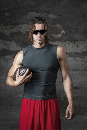 muscle man is wearing sunglasses and holding football ball Stock Photo - 21185849