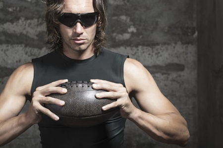 bare chested: football player is wearing sunglasses and holding ball in hands
