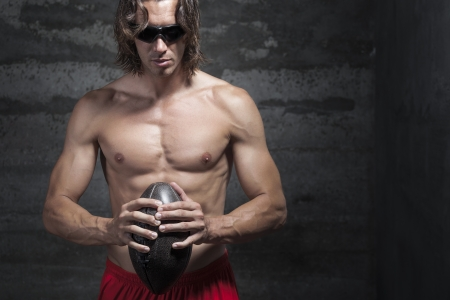 bare chested: bare chested long hair muscle man is wearing sunglasses and holding football ball in hands