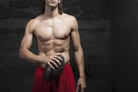 gaze: bare chested muscle man is wearing sunglasses and holding football ball in hands