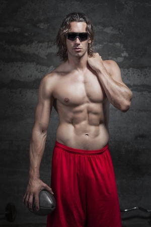 bare chested: bare chested muscle man is wearing sunglasses and holding football ball in his hand