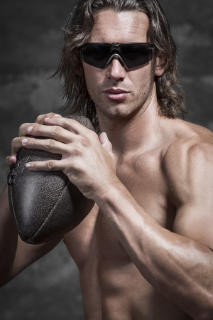 rugby player: half lenght of bare chested muscle man is wearing sunglasses and holding american football ball in his hands